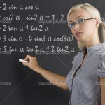 pretty young teacher with blond hair and glasses taking a math lesson on the blackboard