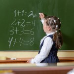 little-girl-by-a-chalkboard-with-chalk-in-her-hand